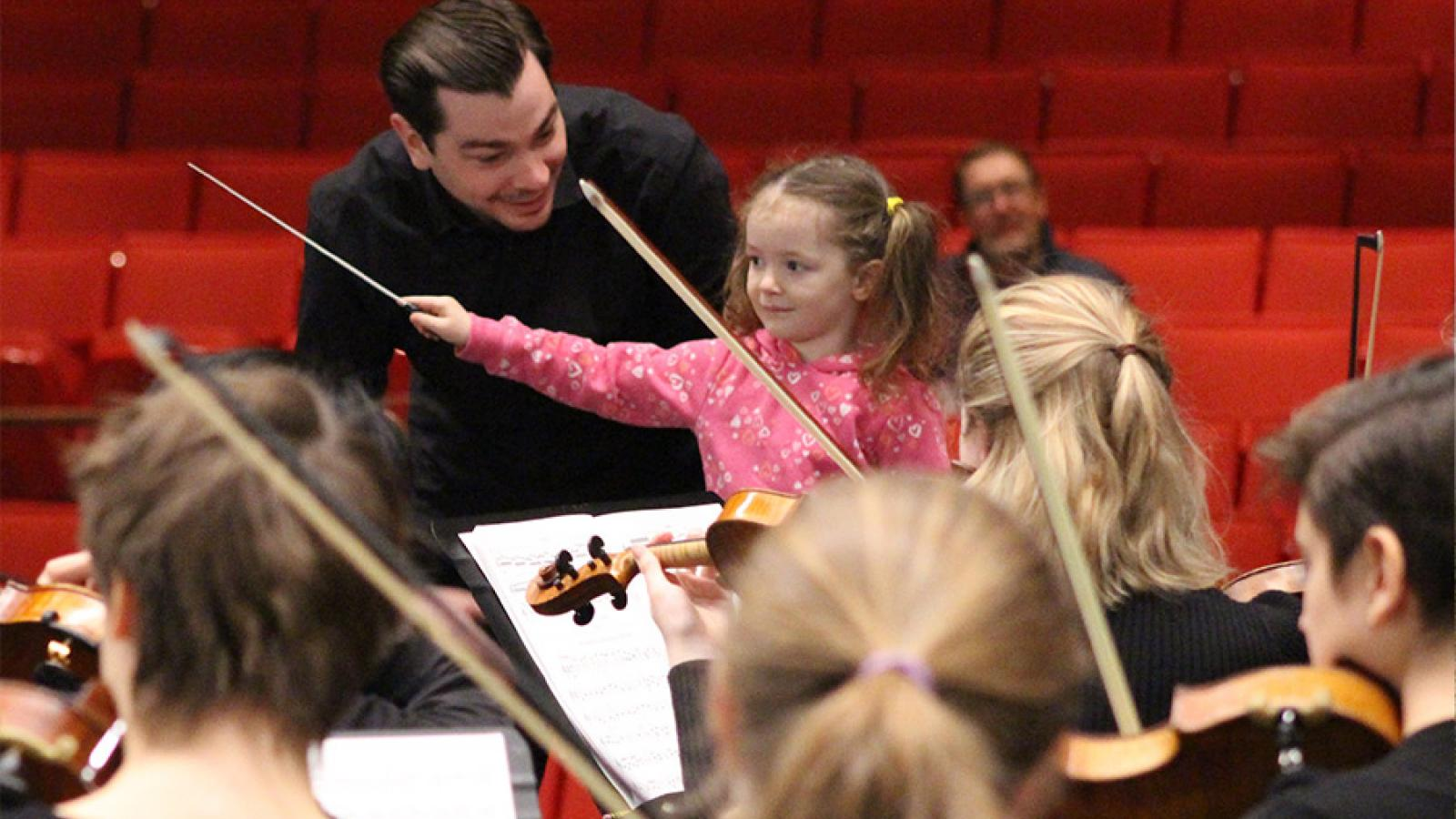 A faculty member teaches a girl how to conduct an ensemble