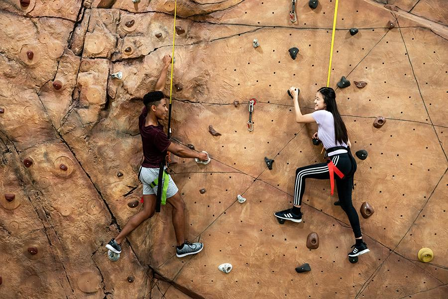 Two Interlochen Arts Academy students scale the climbing wall at the Dennison Center