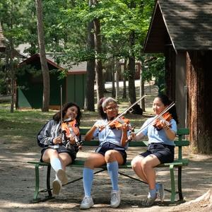 Three violinists rehearse on a bench