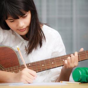 A girl jots down notes while playing guitar